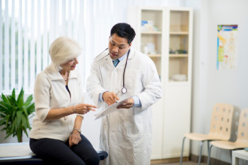 Doctor with a senior patient in an examining room.