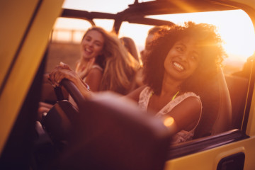 Smiling Afro girl with girl friends on a summer vacation road trip at sunset