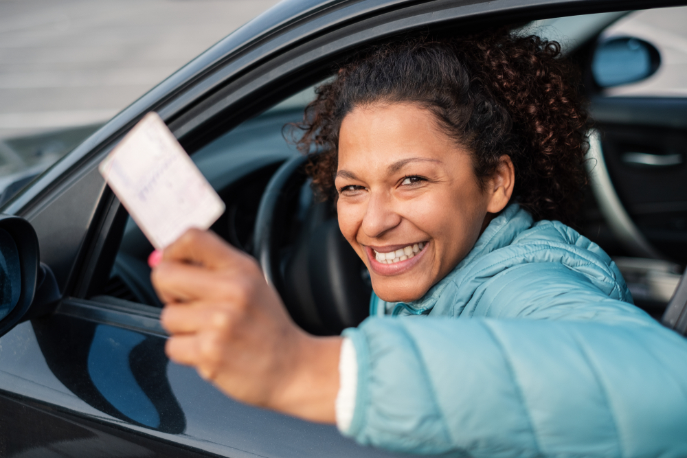 woman holding her reinstated drivers license smiling inside a car thanks to sr22 insurance