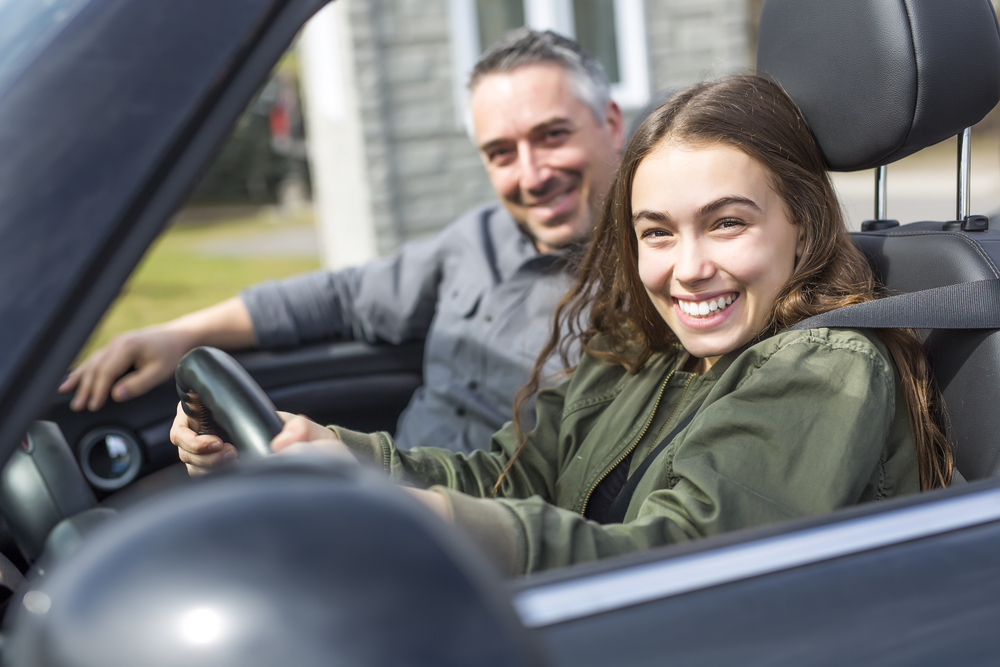 father helping teen daughter first time driving