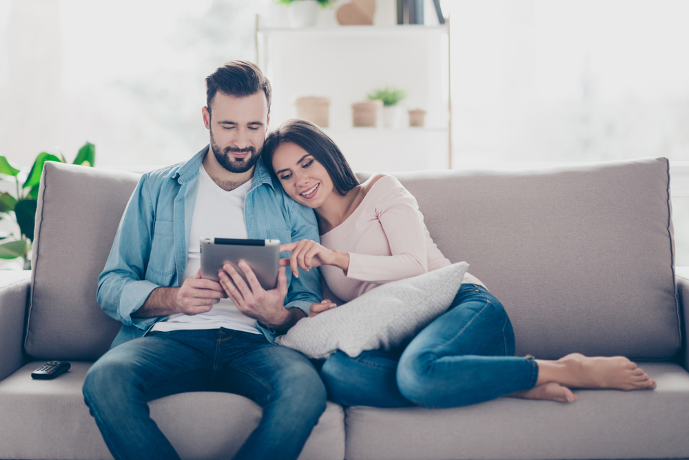 couple in living room looking for cheap car insurance on tablet