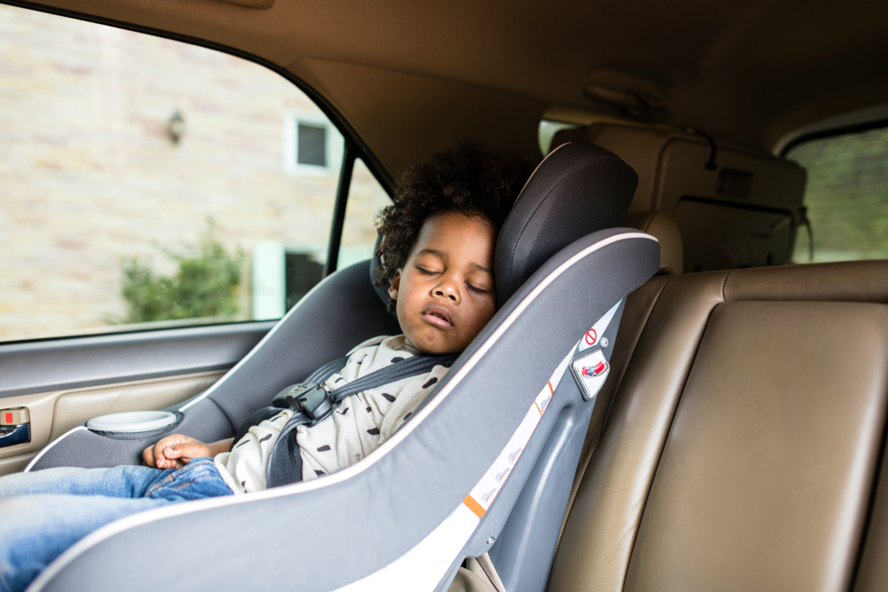 child sleeping on car seat with safety guidelines.