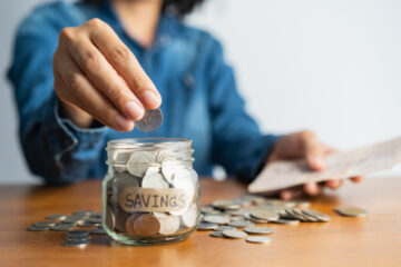 woman putting coins in jar that says savings