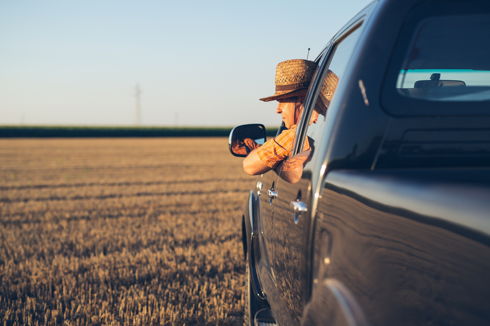 sideview of man with hat drivingpick up truck in a field