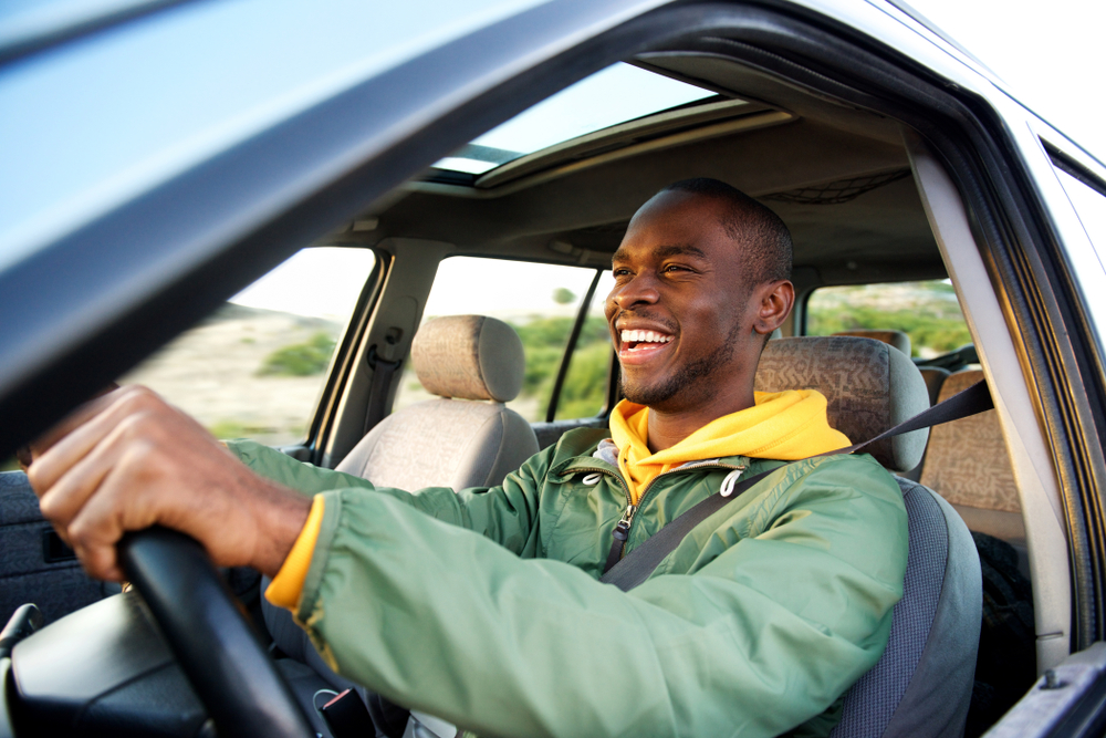 Side portrait of happy african american man driving with car insurance savings