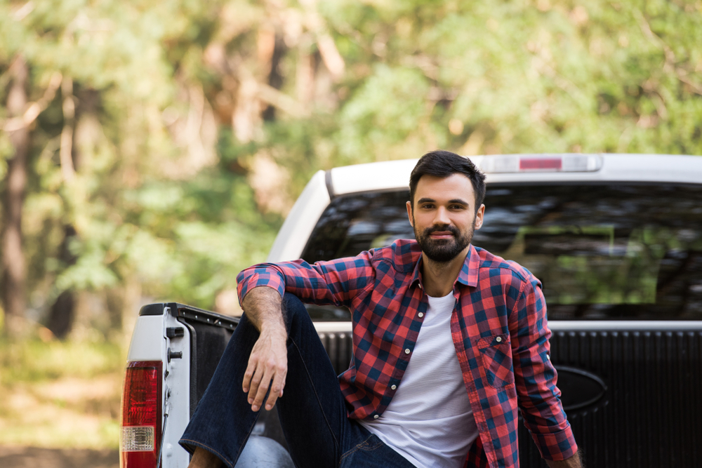 bearded man sitting on pickup truck in nature