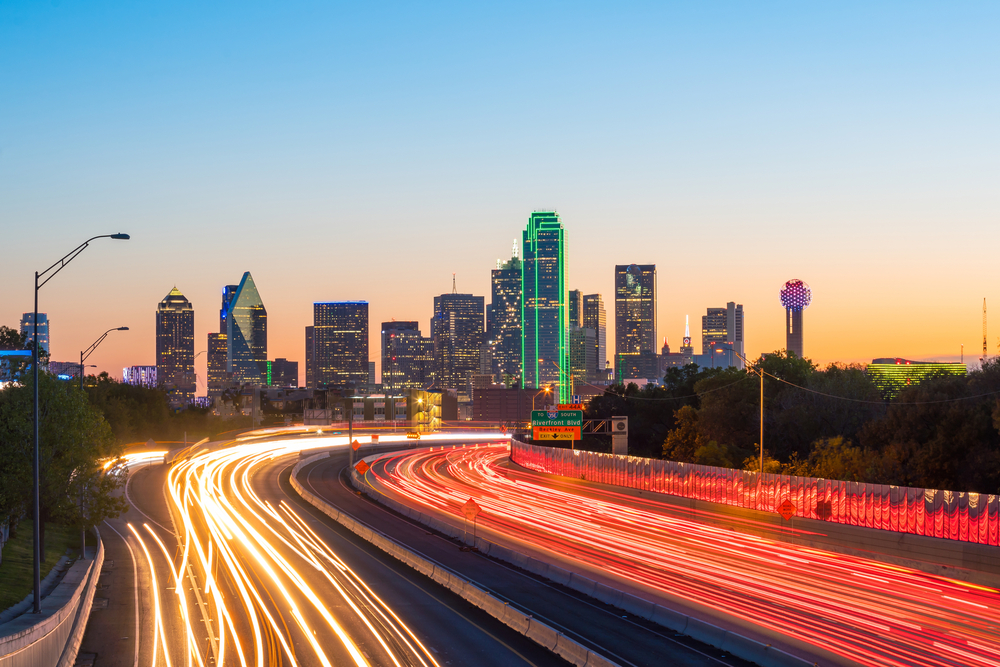dallas skyline at twilight with highway filled with cars with texas car insurance