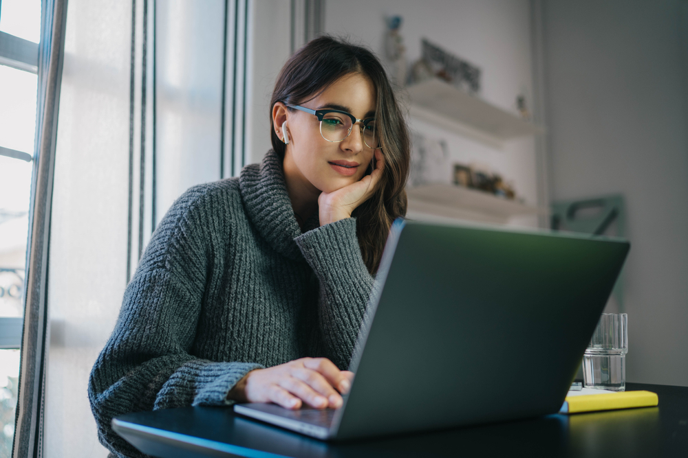 young hispanic woman looking at laptop for car insurance in texas