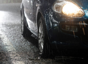 side view of car driving in severe rain