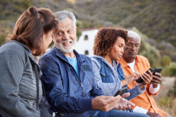 four senior citizens looking at smartphones together