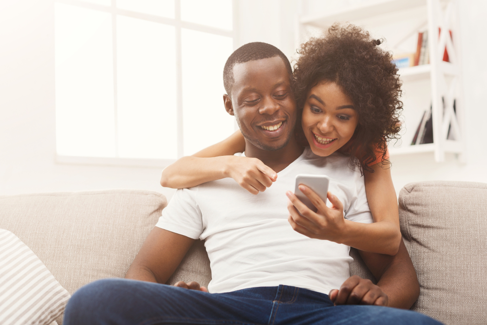 african american couple looking at cars online in phone