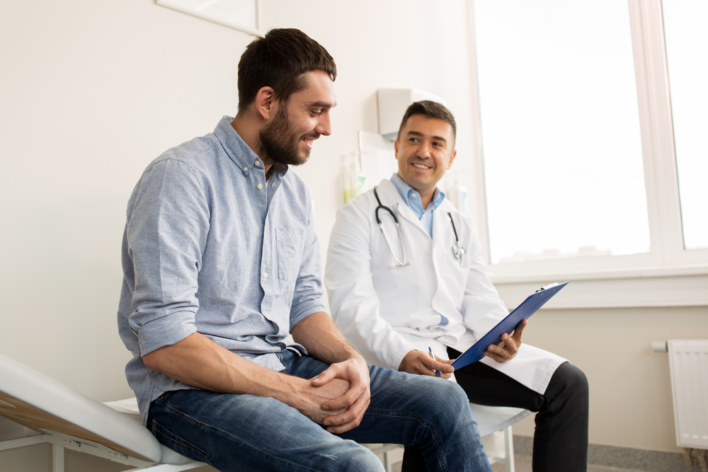 smiling doctor with clipboard and young patient talking about dependent health insurance