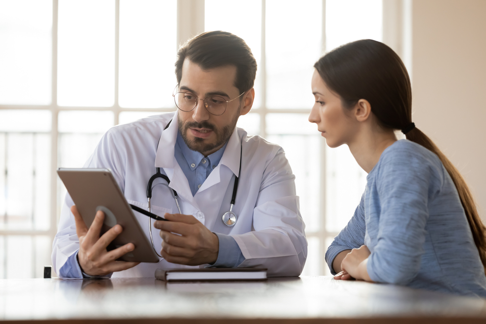 young woman with doctor looking at insurance info on tablet