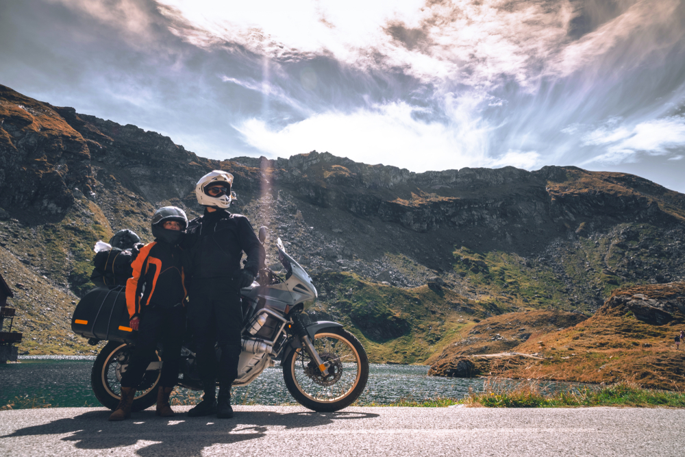 couple in front of motorcycle with a scenic mountain in the background