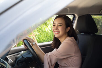 smiling asian young woman driving a car in texas with a teen license