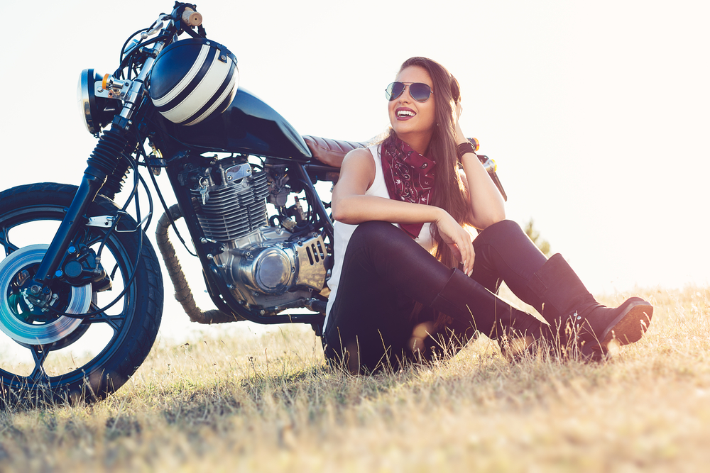 smiling woman sitting in front of her motorcycle in a field