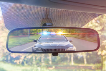 rear view mirror in car with the reflection of a cop car