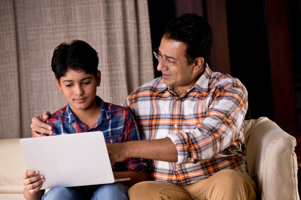 father and teen son looking at laptop to file a teen drivers license in texas