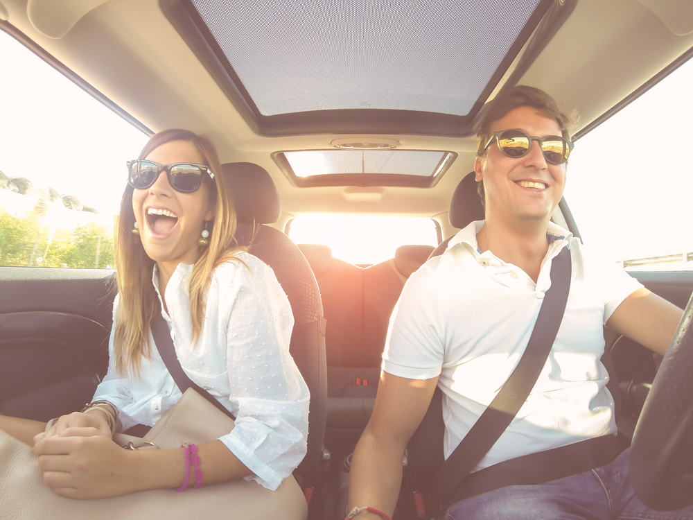 Filtered image of a couple driving at sunset with dallas cheap car insurance