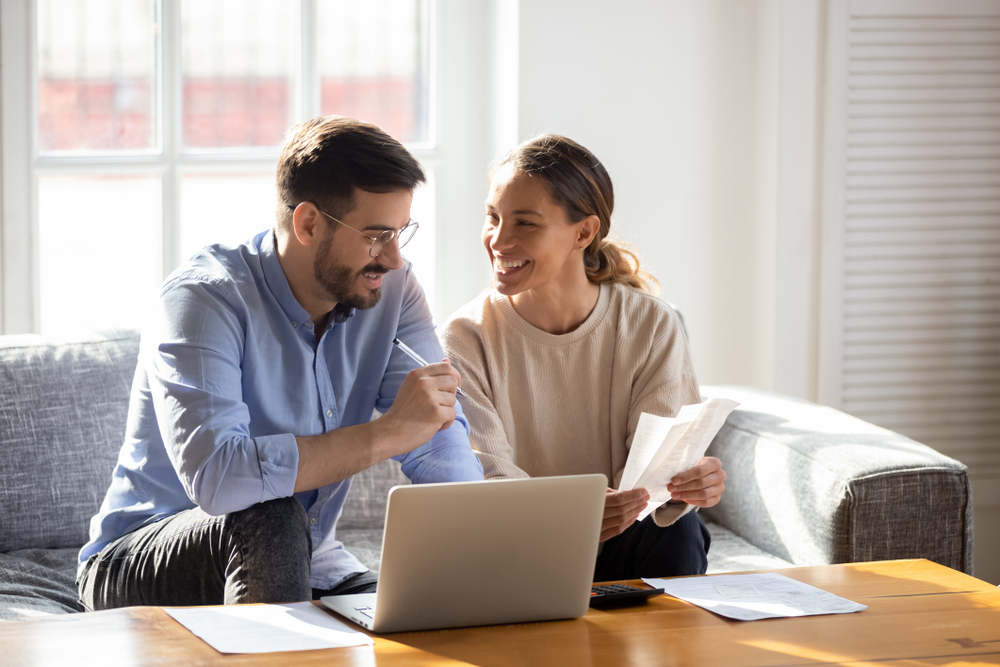 young couple in living room looking for renters insurance in dallas in laptop