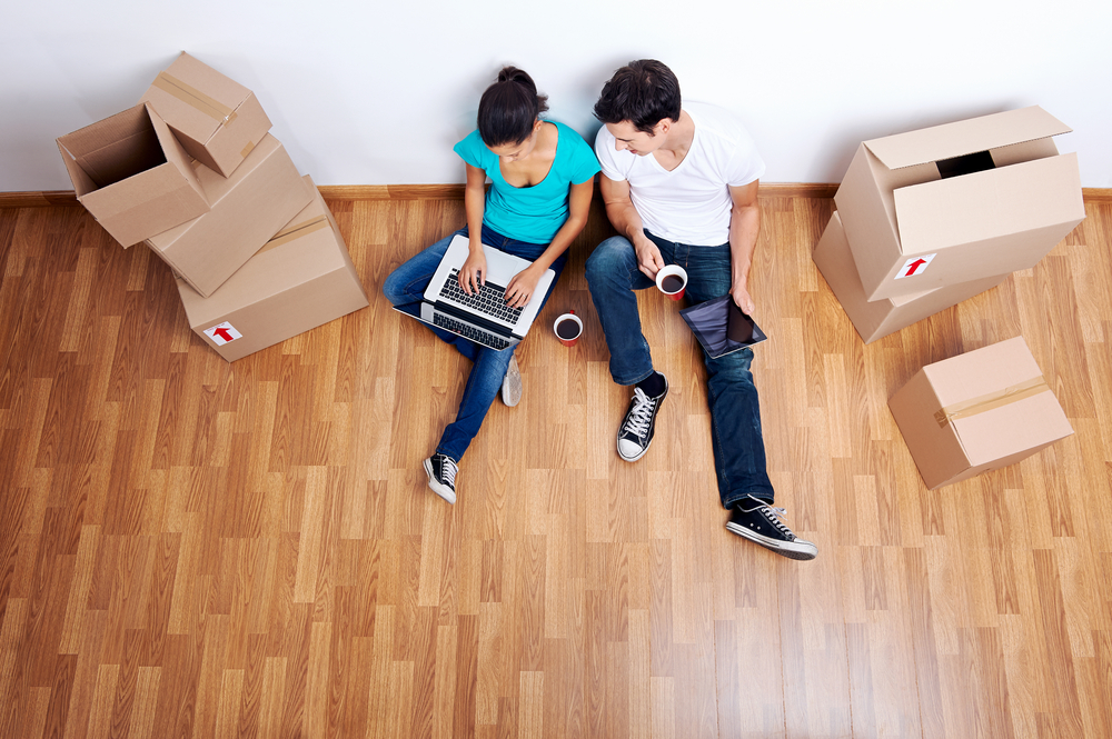 overhead view of couple sitting on floor together using computer