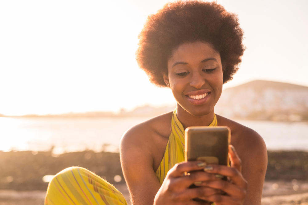 african american smiling woman looking in phone for car insurance