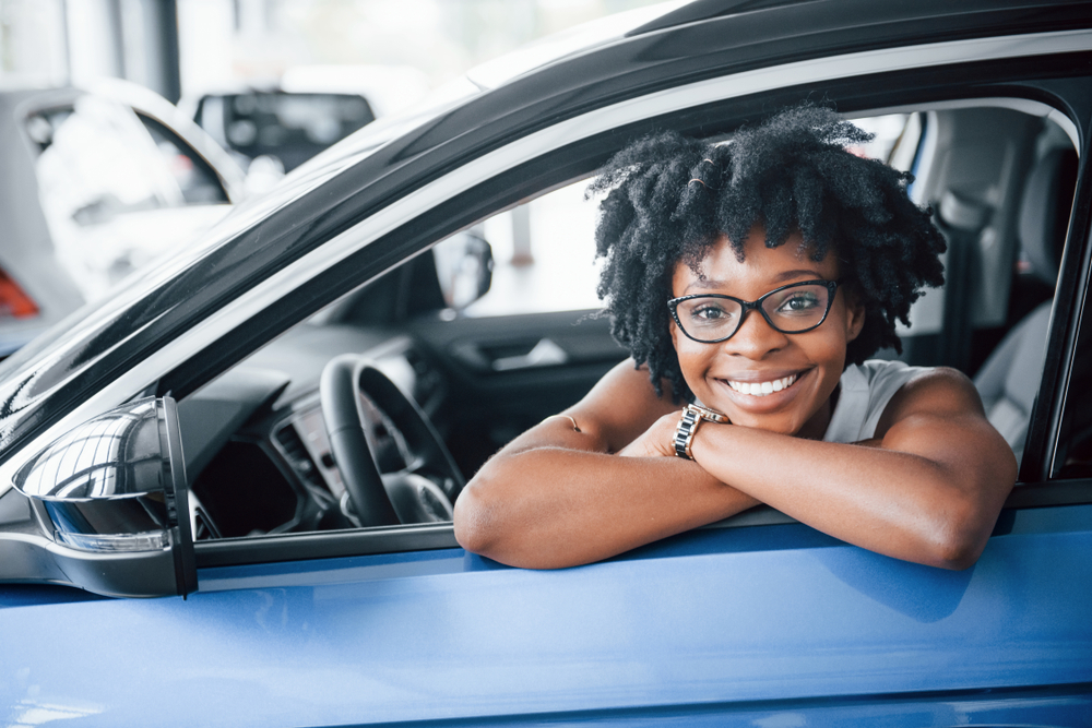 oung african american woman sits inside of new modern car.
