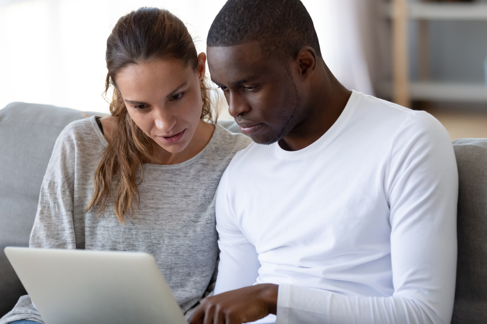 serious couple lookig at renters insurance options at laptop